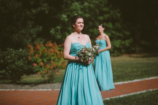 Gorgeous bridesmaids in turquoise walking down the aisle