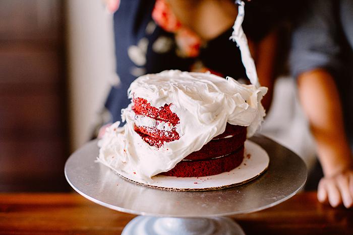 Frosting a red velvet cake