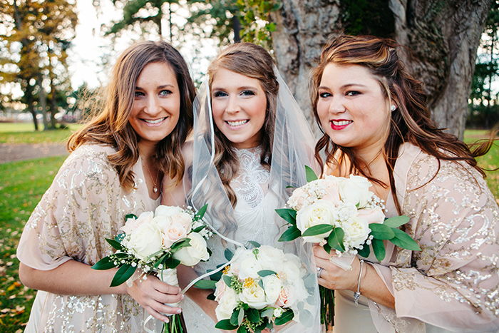 The bride and her bridesmaids in sparkly shawls.