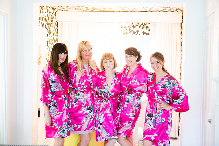 The bride and her bridesmaids in pink robes