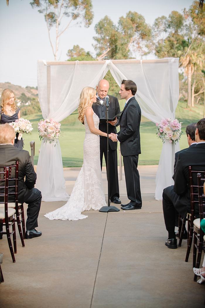 Beautiful wedding ceremony arch with dahlia inspired wedding flower arrangemenets