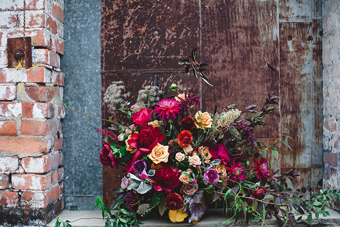 Stunning berry colored wedding bouquet with dahlias and vines