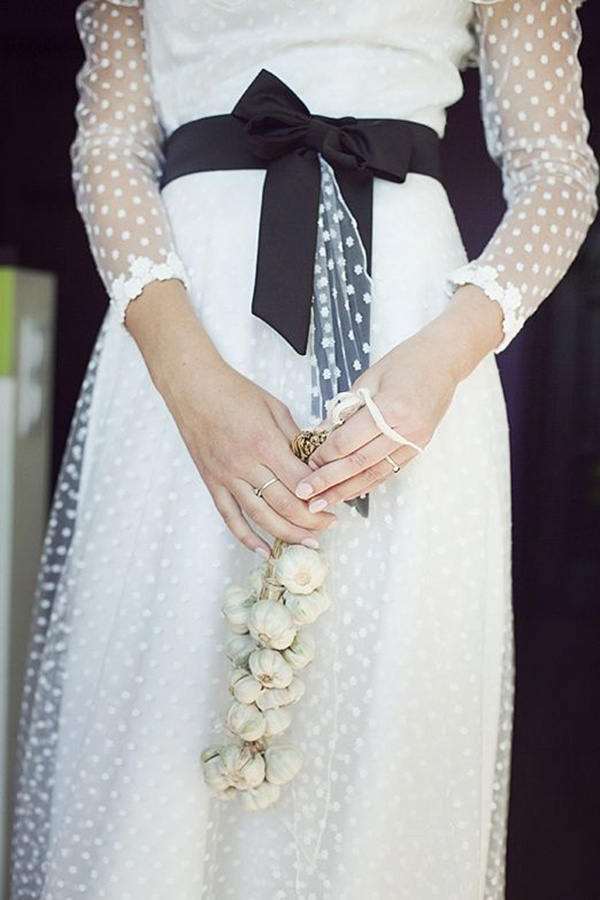 Delicate swiss polka dotted wedding dress with long sleeves and a pretty sash