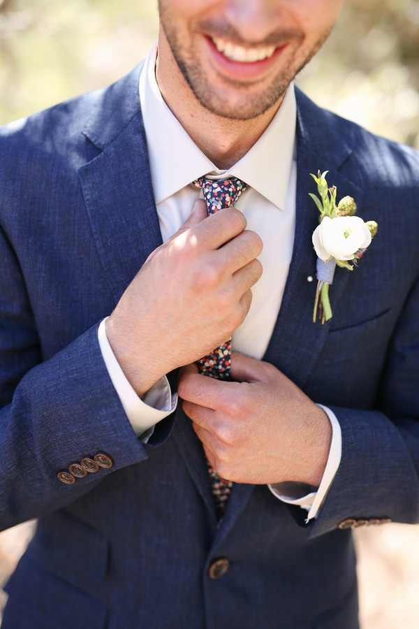 A groom with a colorful tie and simple white boutonniere. Love!