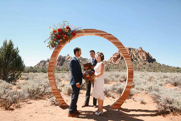 Gorgeous and romantic photo of the bride and groom at their carnival themed desert wedding! The arch is stunning.