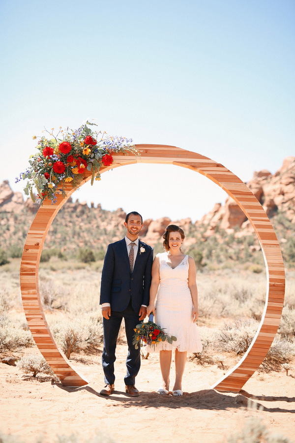 Gorgeous and romantic photo of the bride and groom at their carnival themed desert wedding! How unique is that wedding arch?