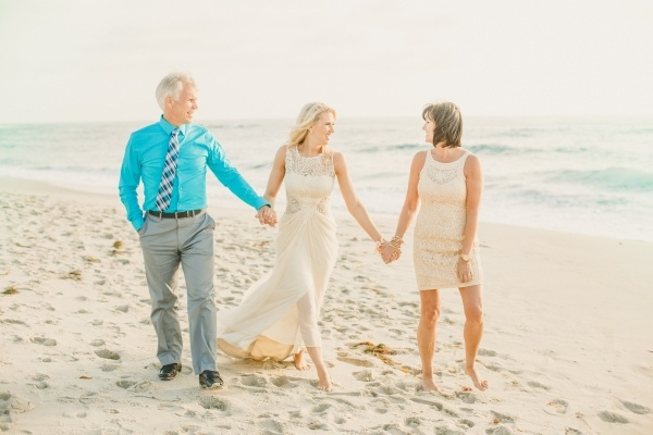 A newly married bride walking down the beach with her parents!