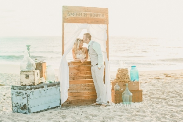 Bride and groom using their ceremony smooch booth backdrop for some adorable photos