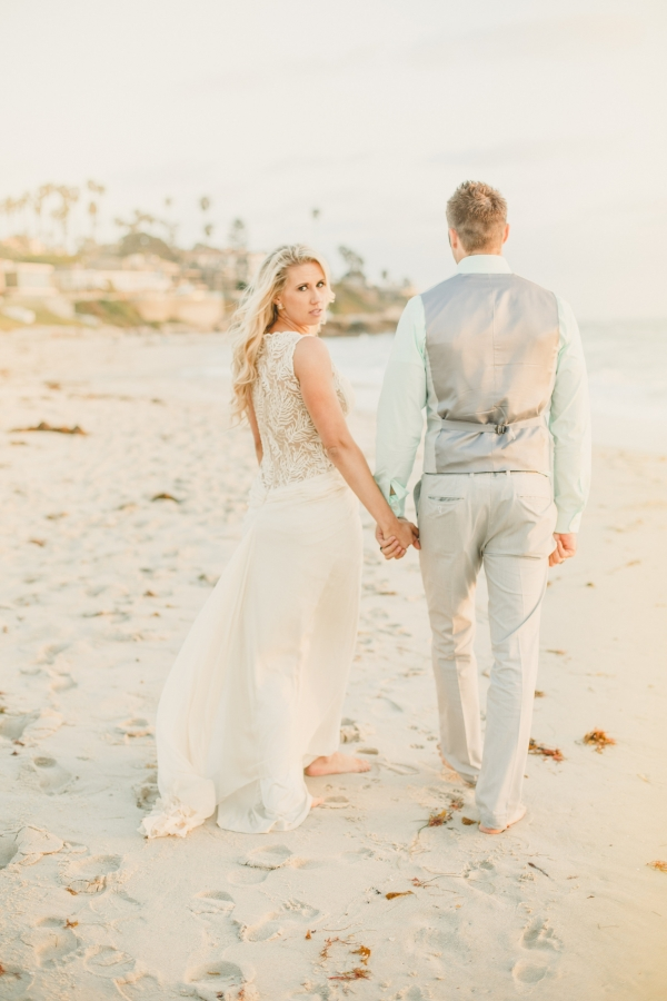 lovely photo of a newly married bride and groom as the walk down the beach!