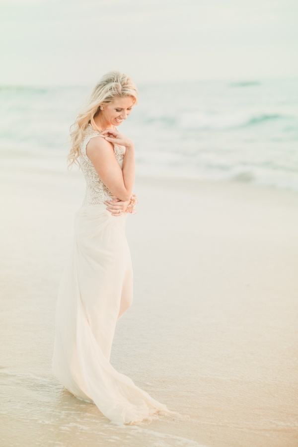 A stunning adorable bride poses by the ocean at her beach wedding!