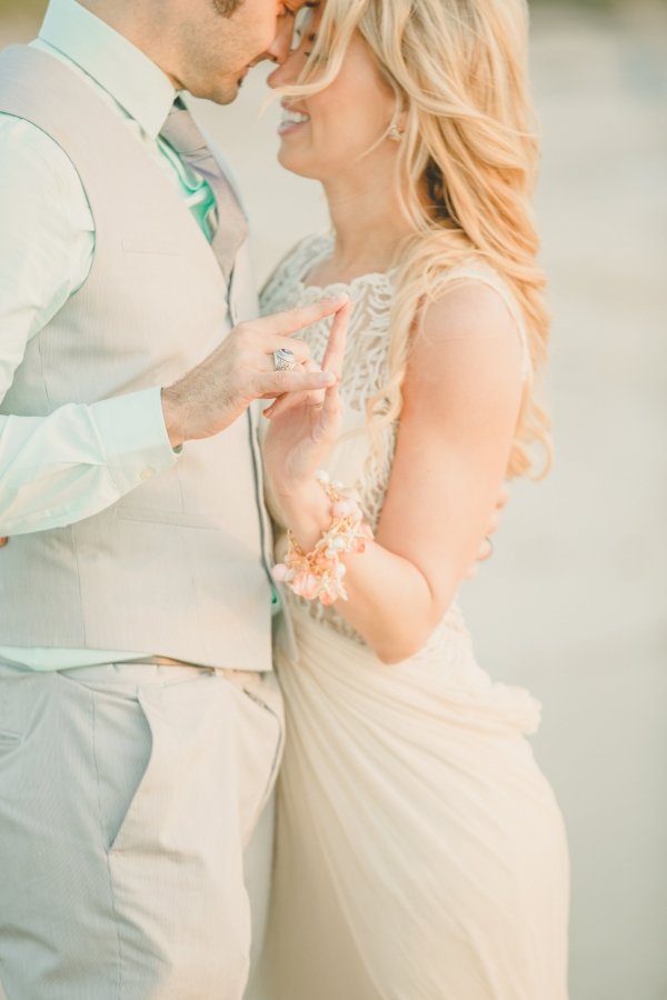 An adorable bride and groom have a tender moment at their beach wedding.