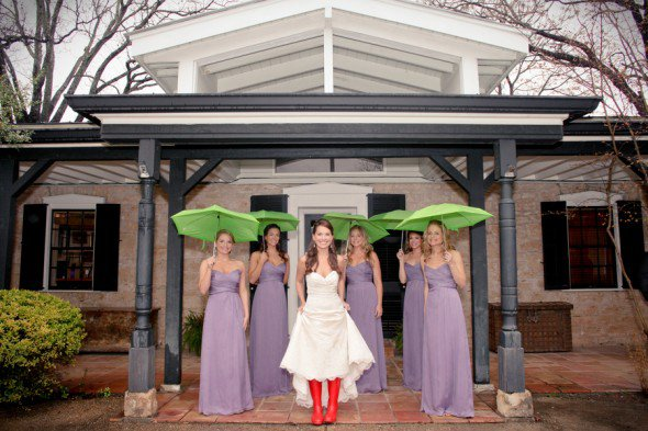 Red rain boots and green umbrellas lead to the best rainy day wedding photo!