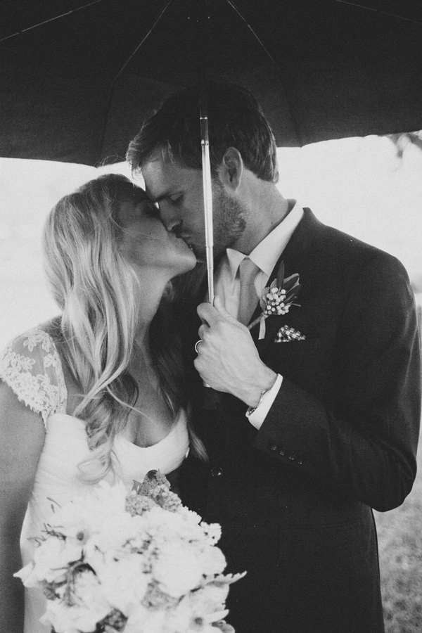 Gorgeous bride and groom embracing in the rain.