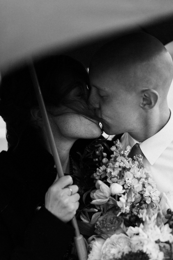 Beautiful rainy day wedding embrace. Learn how to get the best rainy day wedding photos from our post!