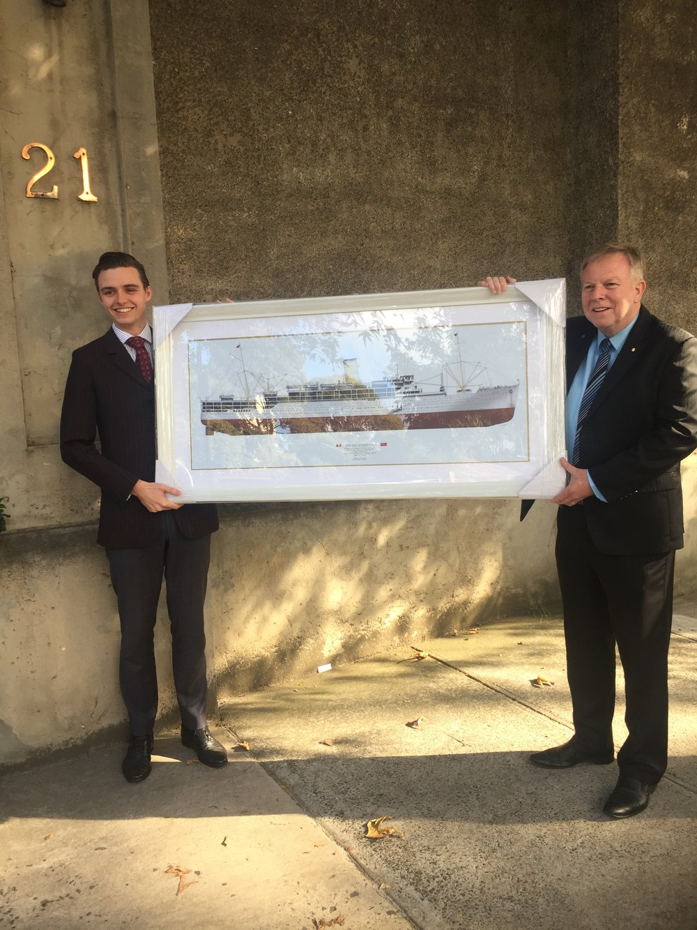 LINER DESIGNS' Chief Illustrator, Michael Brady (left), presenting Mr David Man AM. with a framed print of Stratheden - David's family came to Australia aboard this ship.