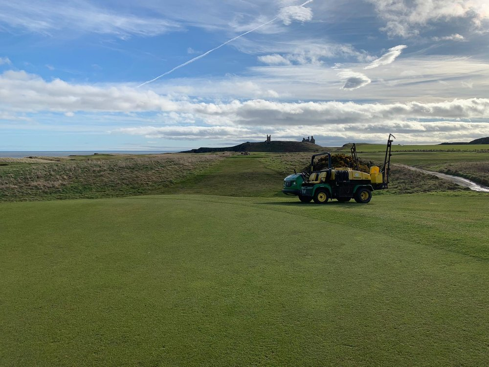Alex out spraying the greens making sure we make the most of the weather!