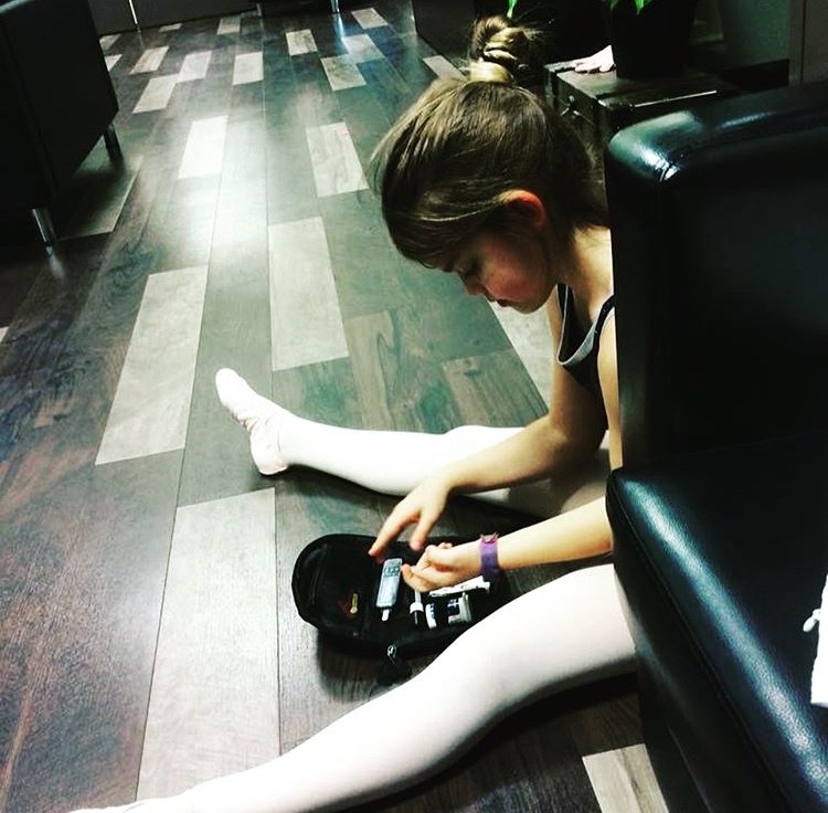 """Dance studio floors are the perfect place for testing our blood sugar. Here is one of our featured """"Sweet Movers"""" Maggie testing in between classes."""