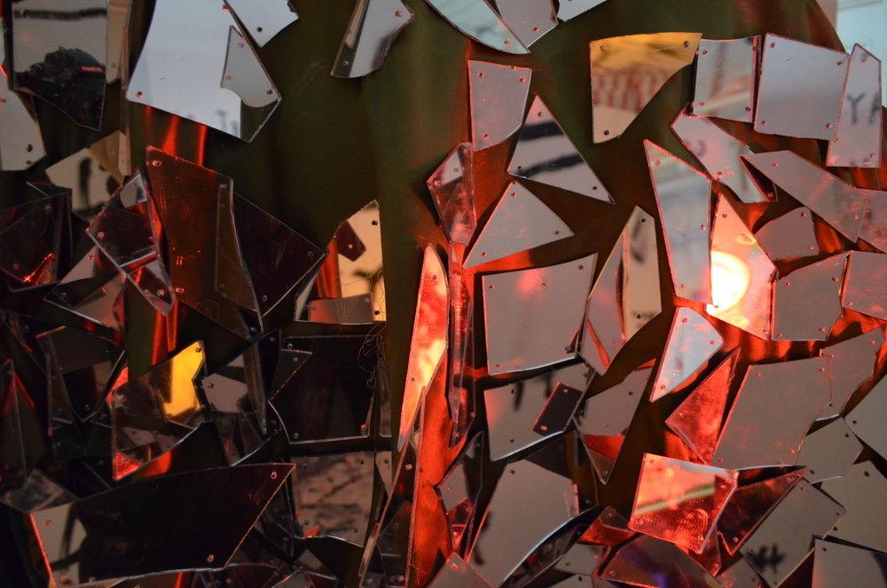 Close-up digital image of mirror cloak       part of the human disco ball in            Get Rich or Die Mayan  performance    [mirrored plexiglas, silky fabric, welded metal hoop swing]