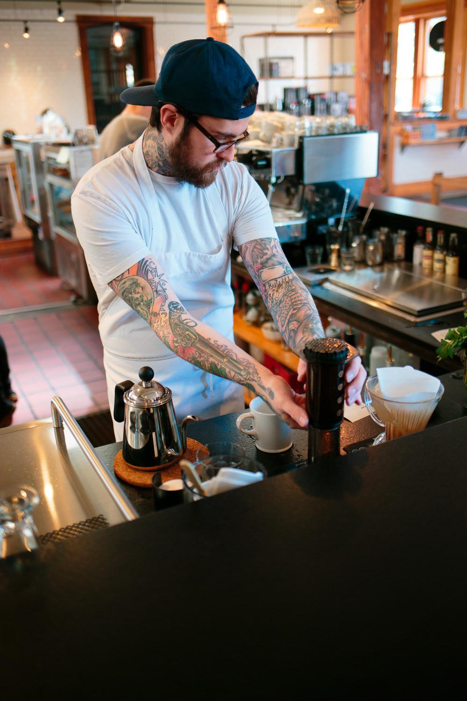 tattooed barista brewing upside down aeropress at utah coffee shop