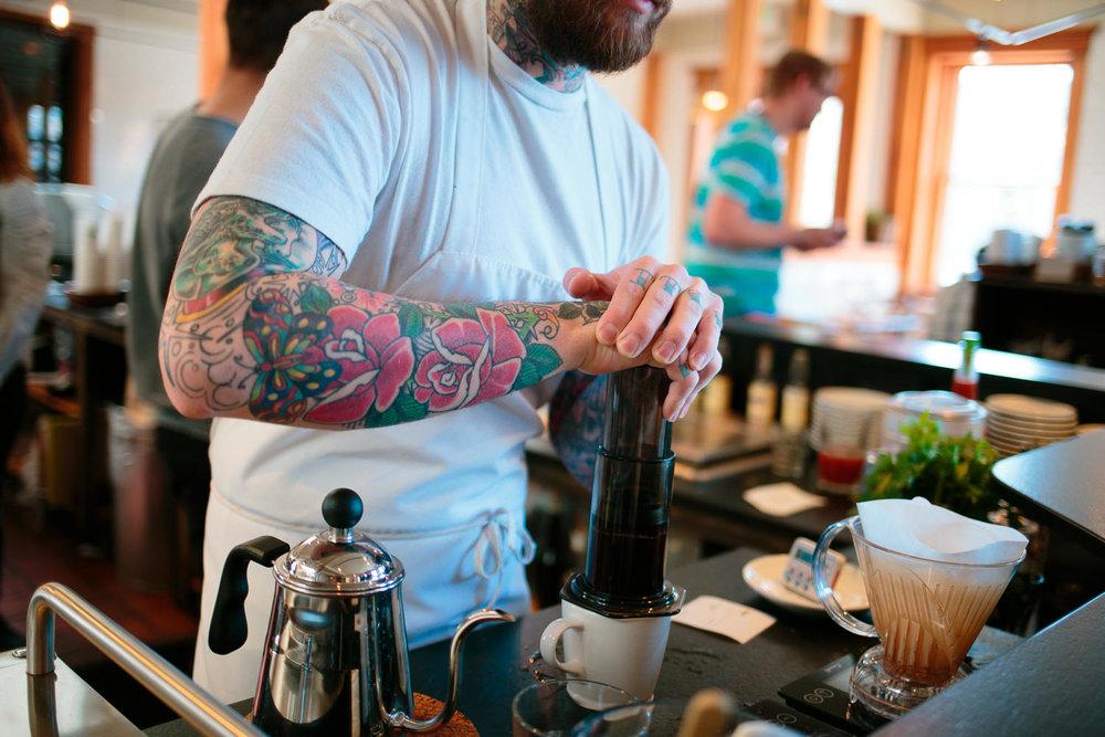 tattooed barista pressing aeropress coffee