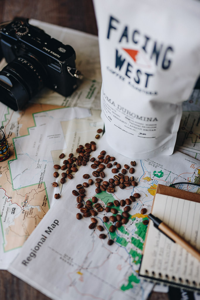 Whole bean coffee on maps with camera and notebook