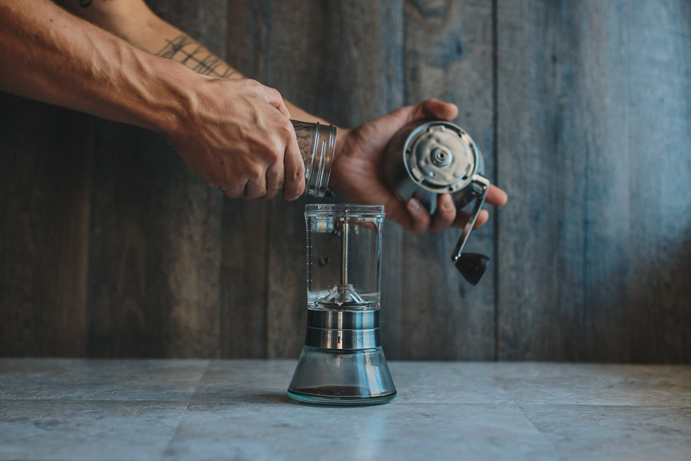 Adding whole bean coffee to handgroud hand grinder
