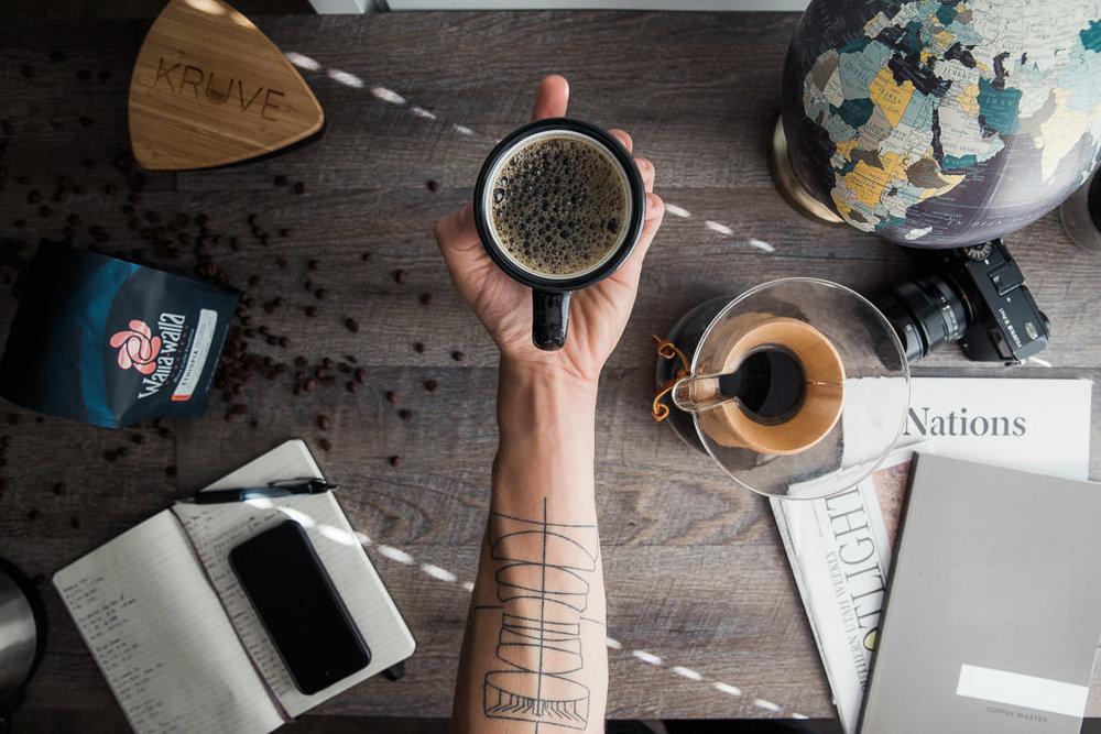 Tattooed barista holds cup of coffee chemex walla walla roastery