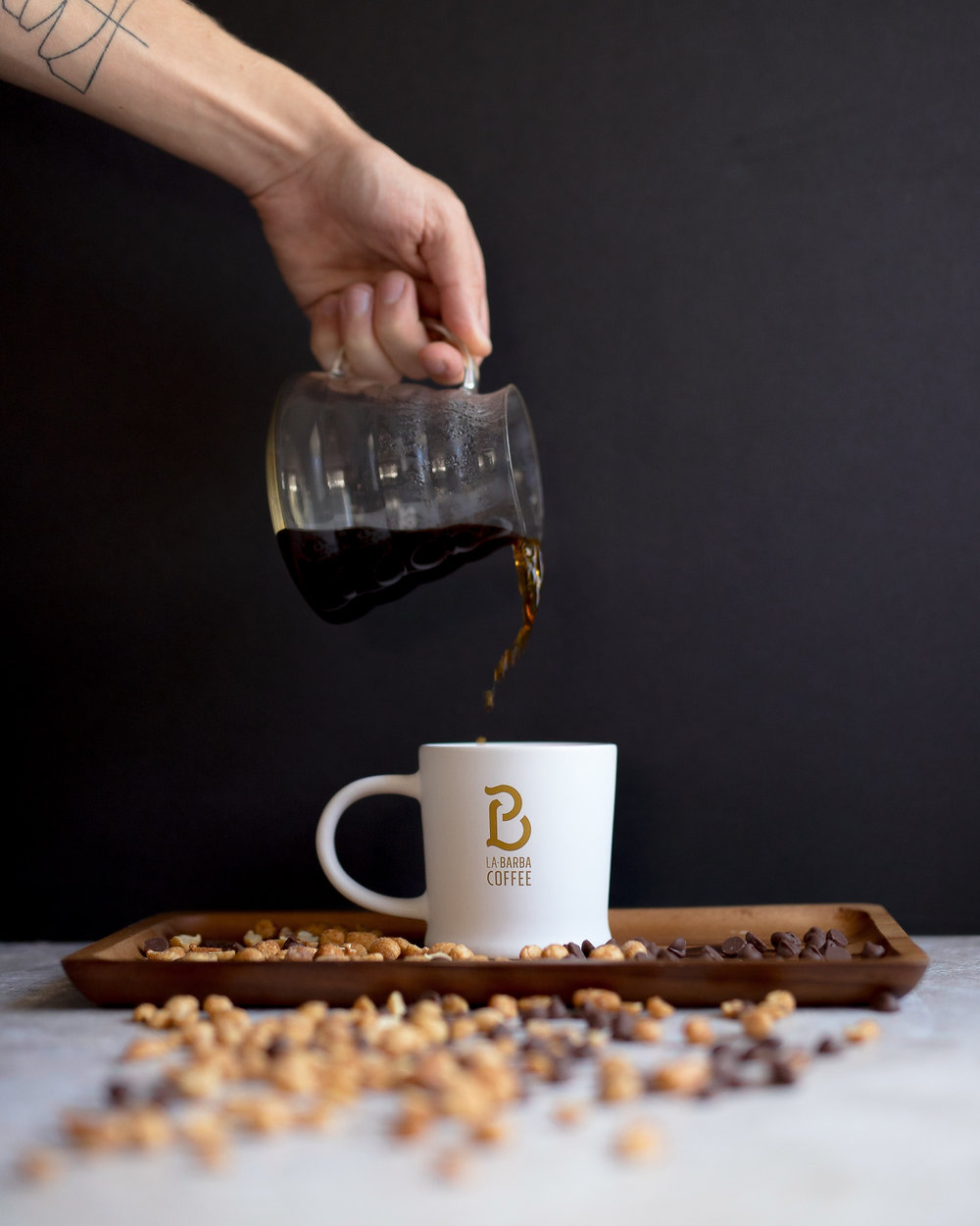 Pouring coffee into mug La Barba utah roaster