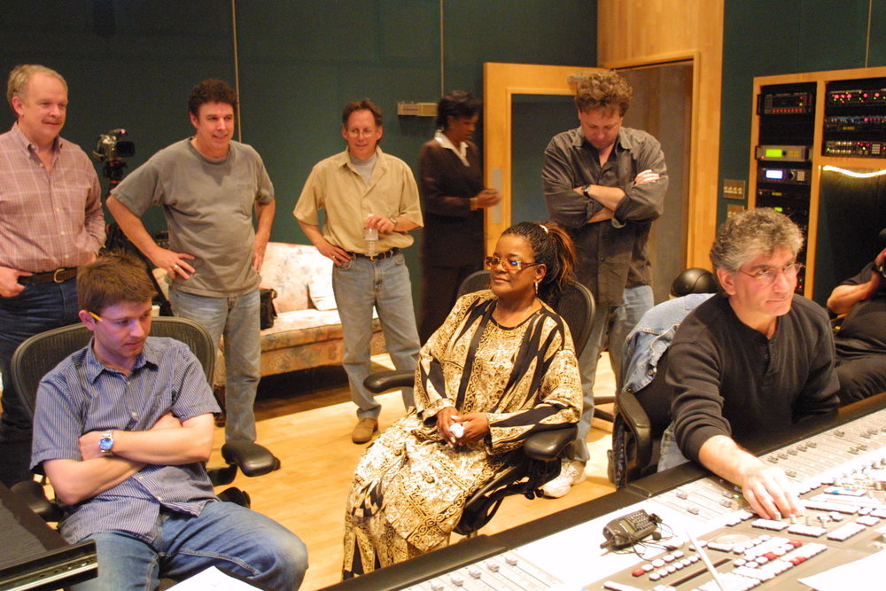 "Jeff Gaskill (standing, arms folded) listening to playback of recording by Shirley Caesar (seated, center) of remake of ""Gotta Serve Somebody"""