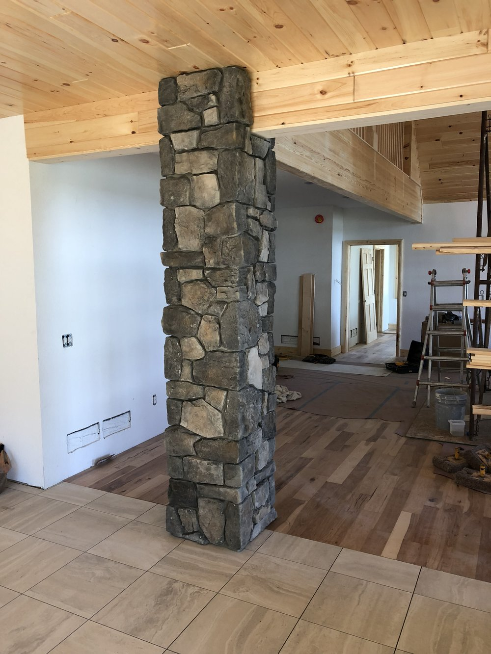 This stone pillar is a beautiful accent in transitioning between the kitchen and living area.