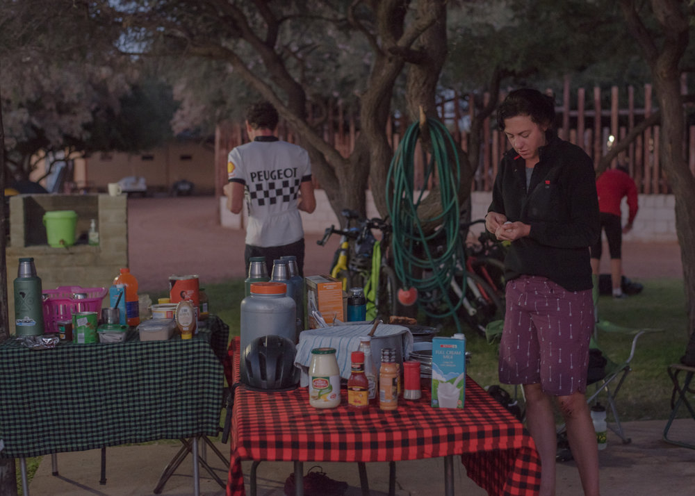 Jen Gurecki grabs breakfast in the cold autumn pre dawn in Botswana. Much of the morning prep on the 68 day African Spokes expedition around camp occurs in the pre dawn darkness, so that cyclists can set out at first light, covering as much ground as possible before the heat of the day sets in.