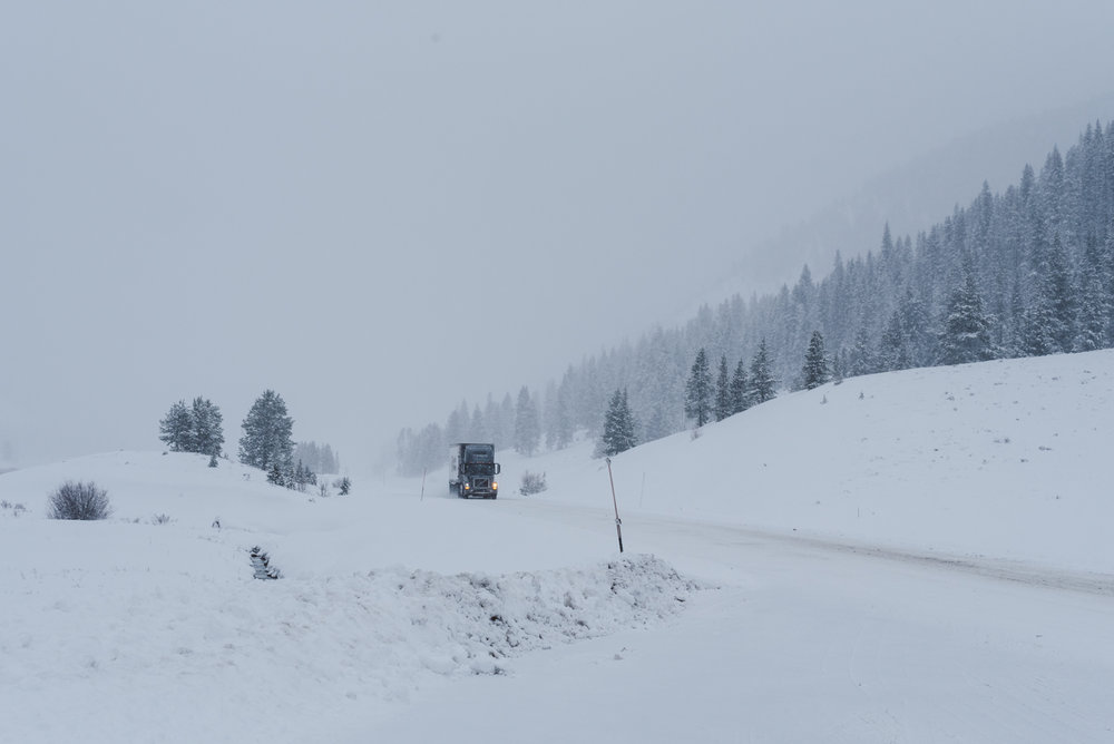 Ice road trucker style through Yellowstone, slow and steady, with hazards flashing in the midst of a blizzard.