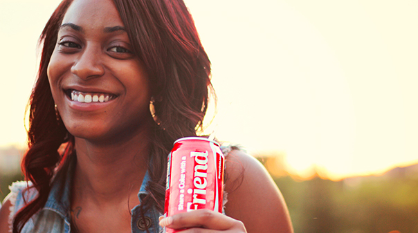A smiling woman is shown holding a can of Coke.