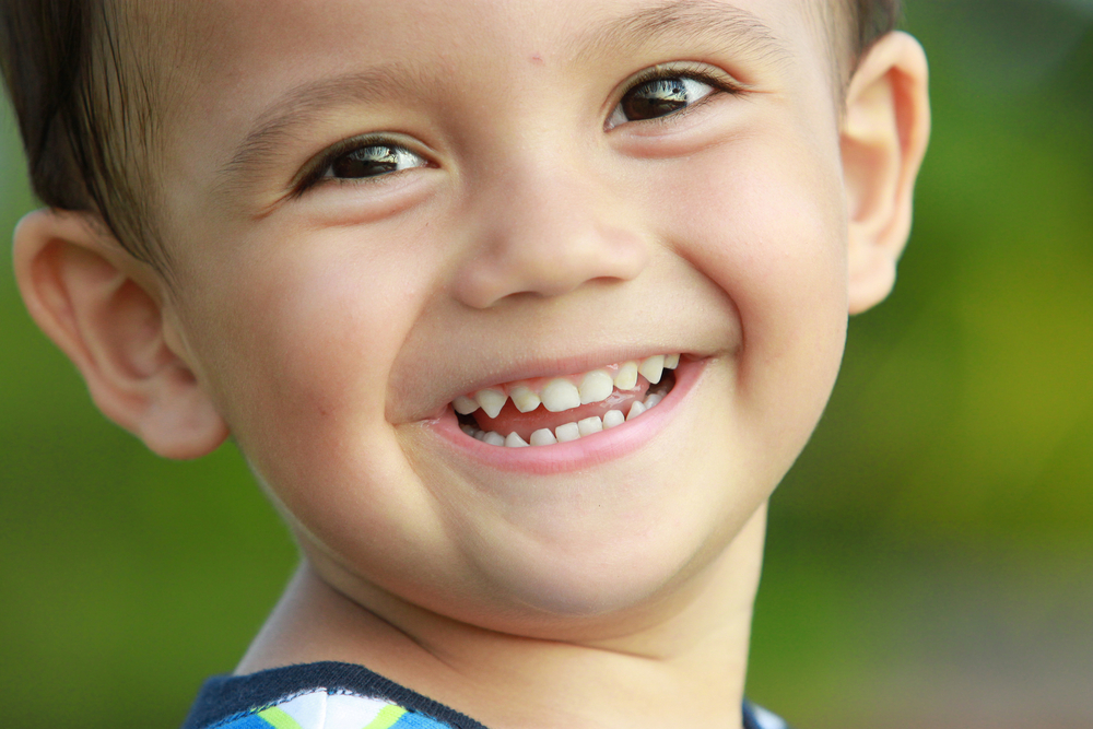 This is a picture of a smiling young boy with baby teeth.