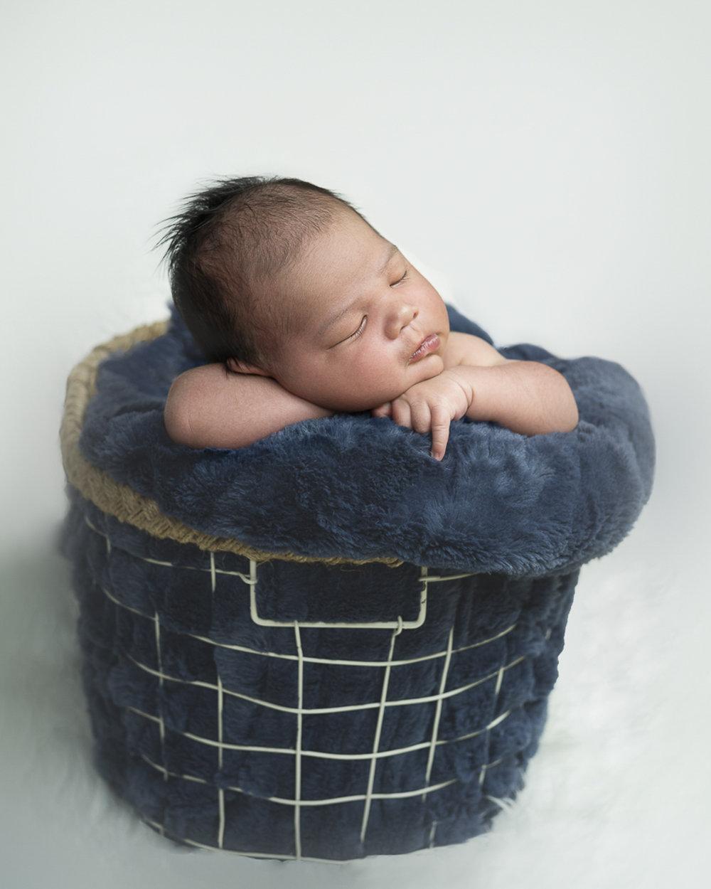 Newborn boy basket pose by NP Photography