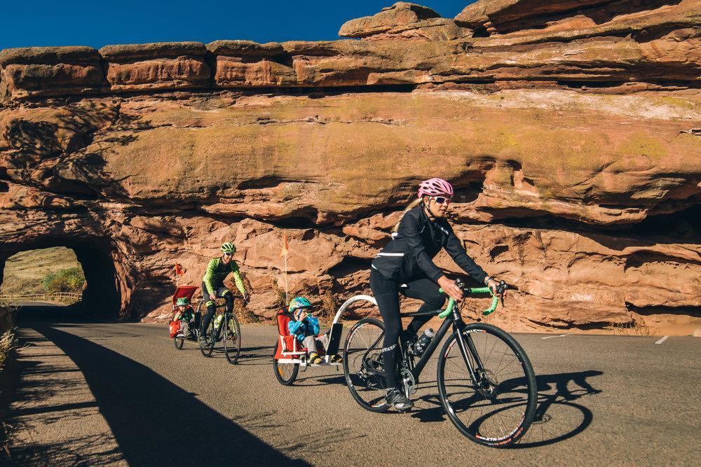 Mom and Dad with Weehoo® BLAST™ bike trailer and TURBO™ trailer bike.
