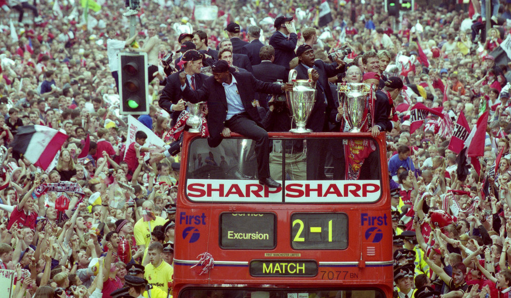 The champions celebrate their treble on the streets of Manchester.