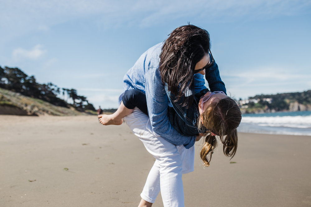 mom holding 5 year old daughter and dipping her down while at Baker beach {SF Family Photographer}