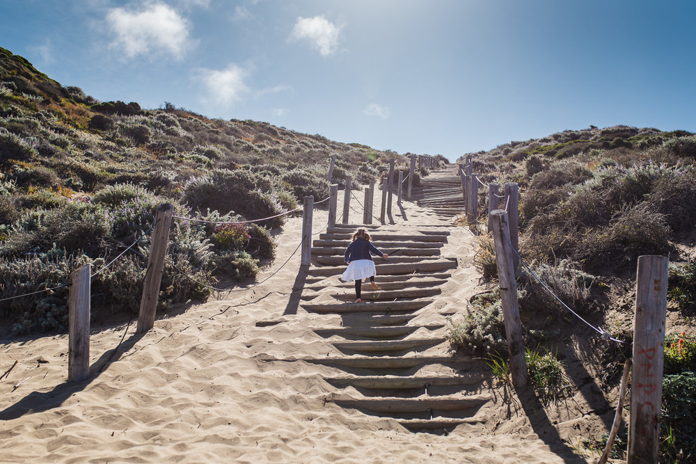 five year old girl climbing up sand stairs at Baker beach {Bay Area On-Location Family Photographer}