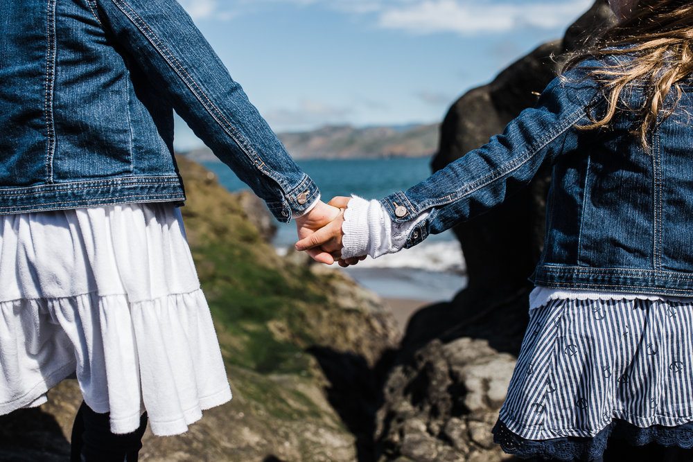 five year old twin girls holding hands and looking out at the ocean at Baker Beach {San Francisco Lifestyle Family Photographer}