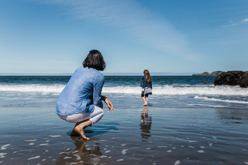 Mom squatting down on the beach watching her five year old daughter wade in the water at Baker Beach {Bay Area Family Photographer}