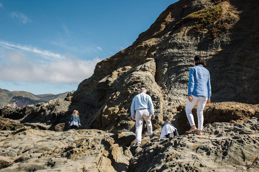 Family of four climbing on the rocks together at Baker Beach {San Francisco Lifestyle Photographer}