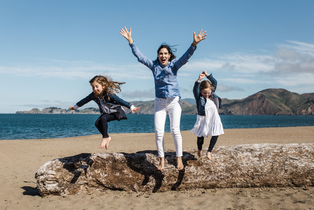 mom and twin five year old girls jumping off of a large piece of driftwood at Baker beach {Bay Area Family Photography}