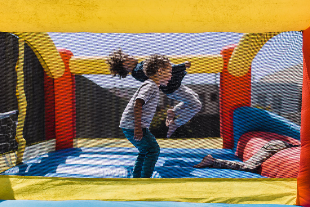 two boys jumping together in bouncy house {San Francisco Family Photographer}