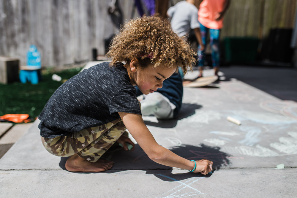 girl drawing on concrete with sidewalk chalk {San Francisco Family Photographer}