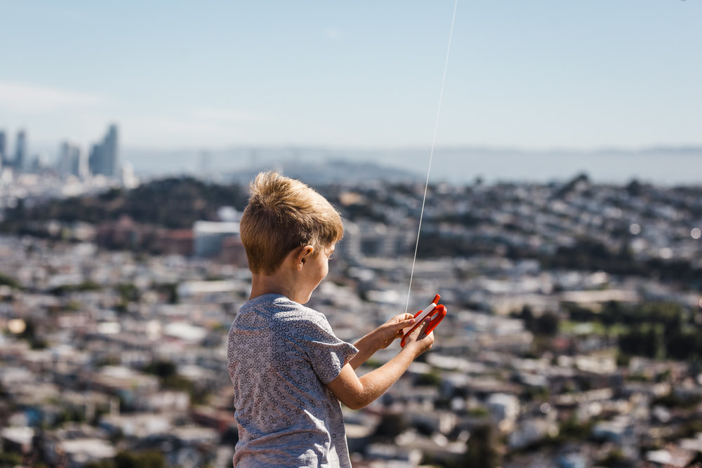 five year old little boy holding his kite with a view of the city in the background {San Francisco lifestyle Family Photographer}