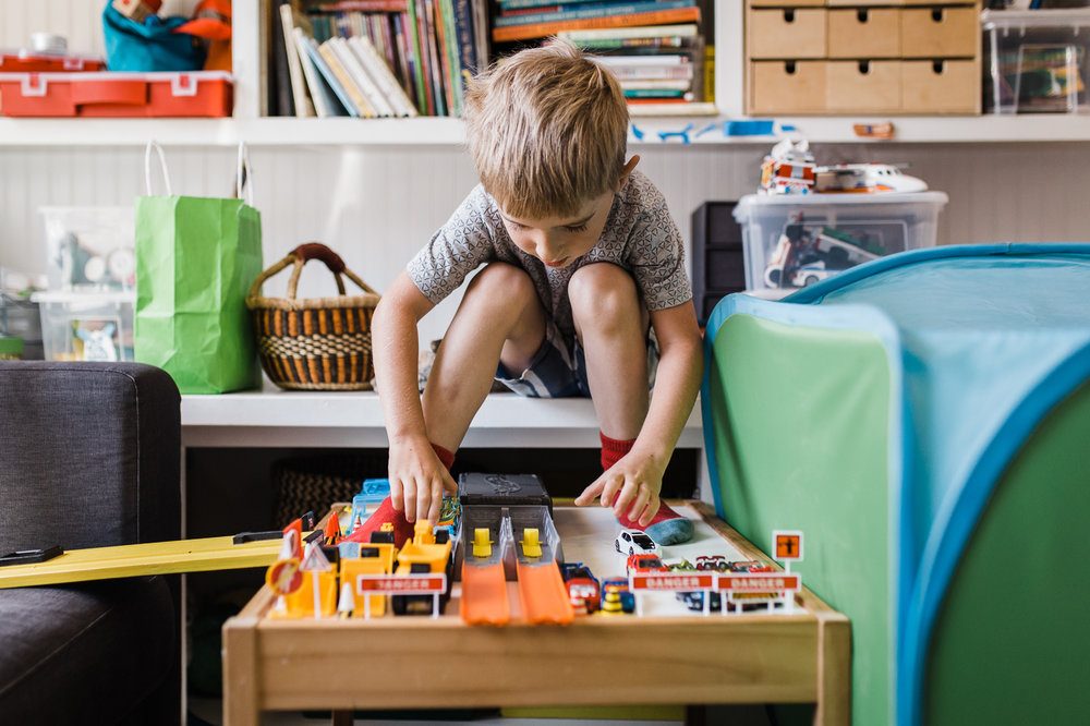 five year old boy sitting on a shelf while playing with his cars - his feet propped up on lego table {San Francisco in-home Family Photographer}
