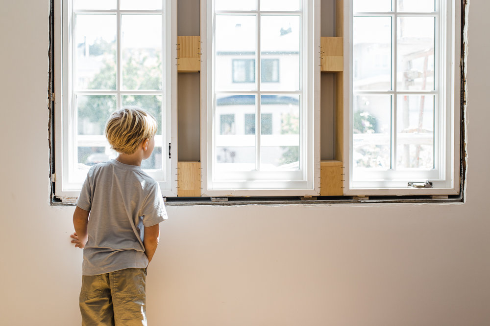 a five year old boy looking out the window of his bedroom still under construction {East Bay Family Photographer}