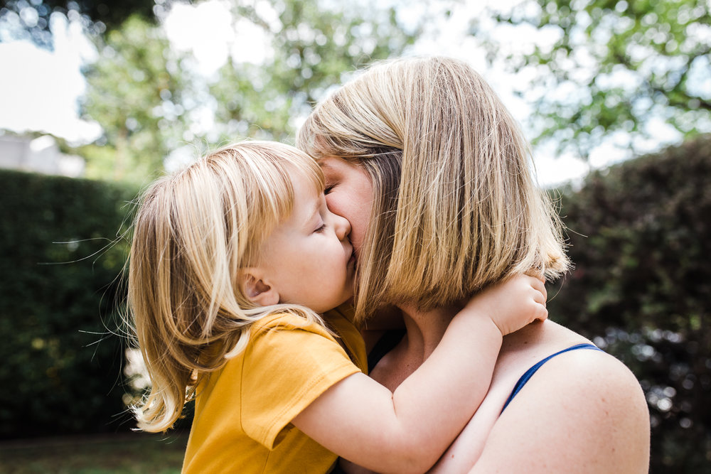 close up of a three year old little girl giving her mom a sweet kiss {East Bay in-home lifestyle Family Photography}