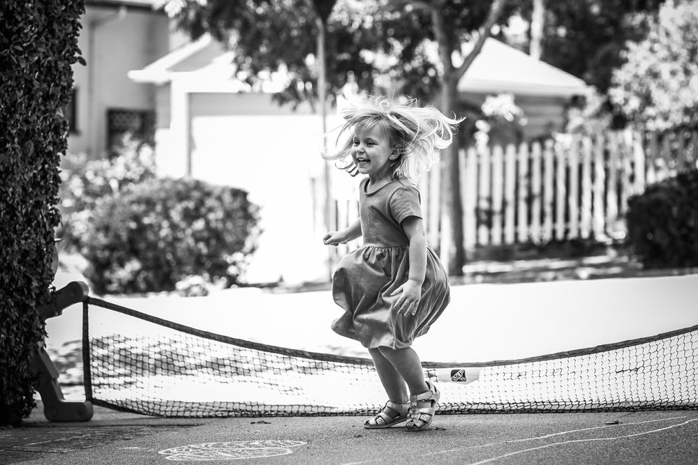 black and white photo of a three year old little girl jumping on the driveway of her house {Oakland in-home lifestyle Family Photographer}